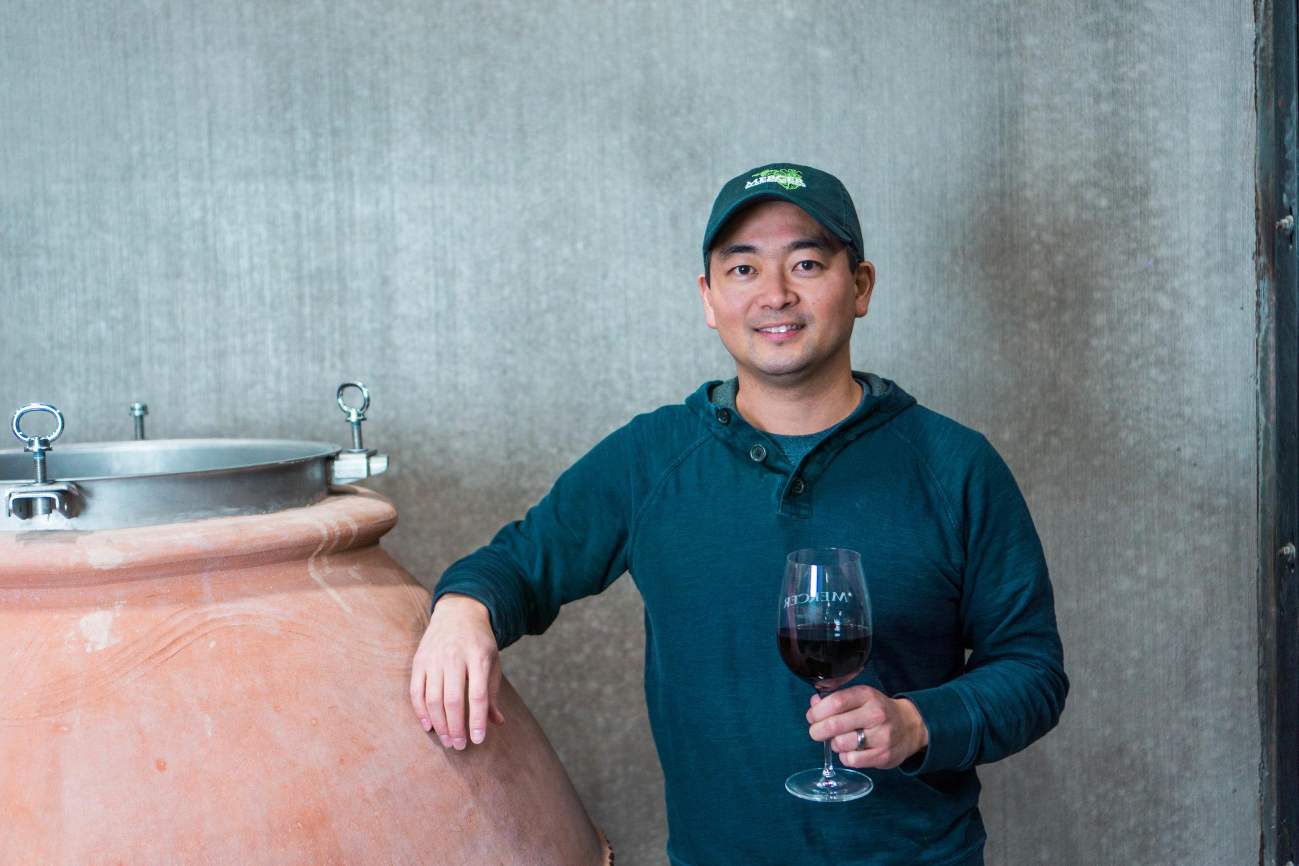 Winemaker Jeremy Santo holding a glass of red wine, leaning on a clay amphorae